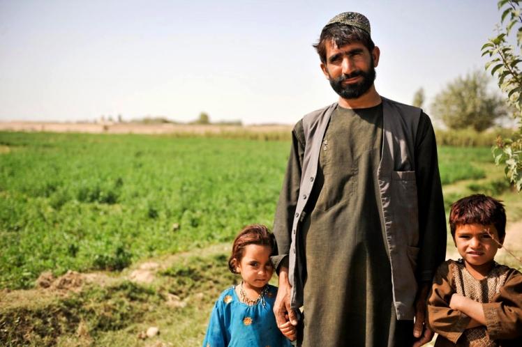 An Afghan farmer stand with his children at a farm in Lashkar