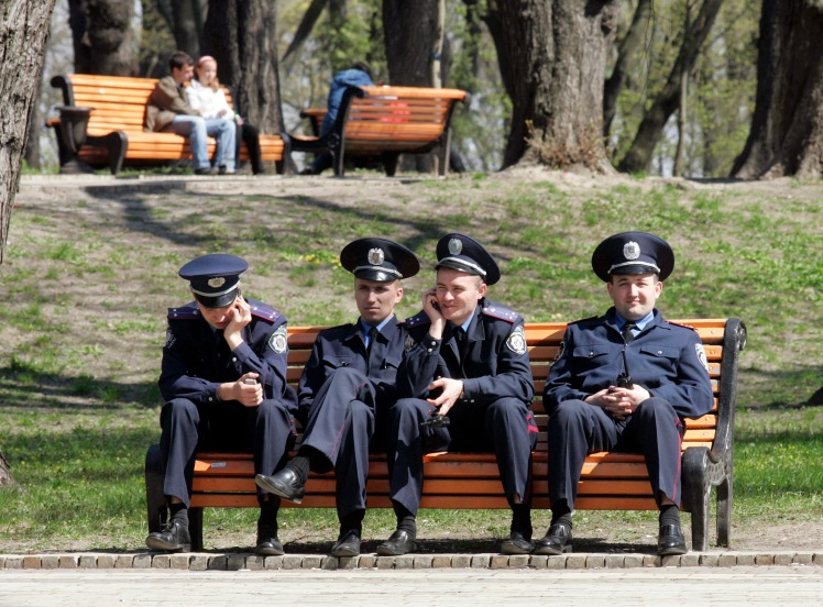 Police officers rest in a central park in Kiev