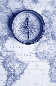 A compass on a vintage map, blue-toned.