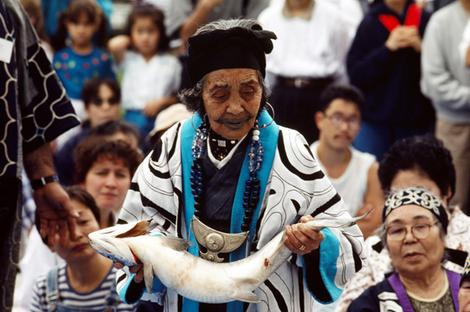A traditionally dressed Ainu woman takes part in a salmon ceremony