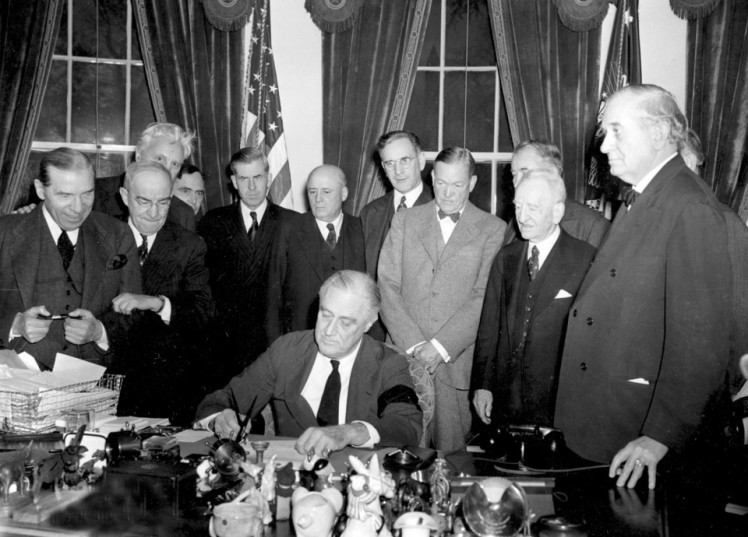 President-Roosevelt-signs-the-declaration-of-war-following-the-Japanese-bombing-of-Pearl-Harbor-at-the-White-House-in-Washington-D.C.-on-December-8-1941.-AP-Photo-960x690
