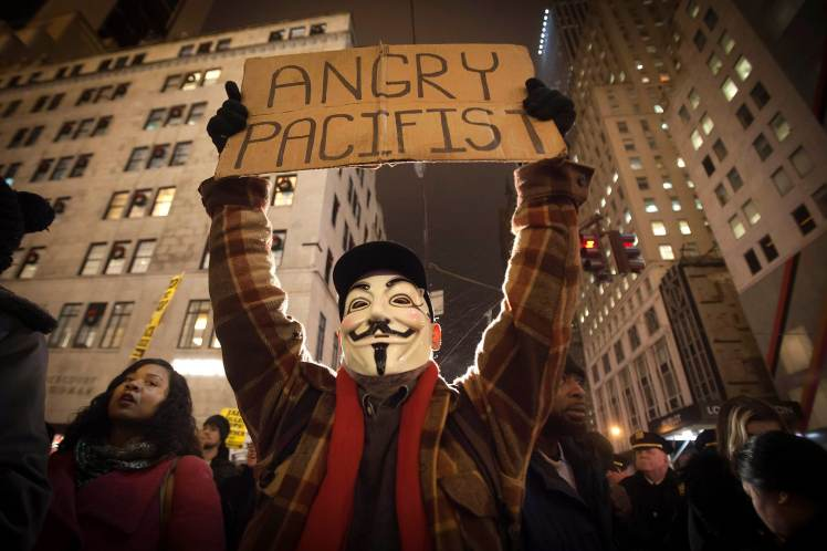 A demonstrator wearing a Guy Fawkes mask walks up 6th Ave as he protests against the police in Manhattan