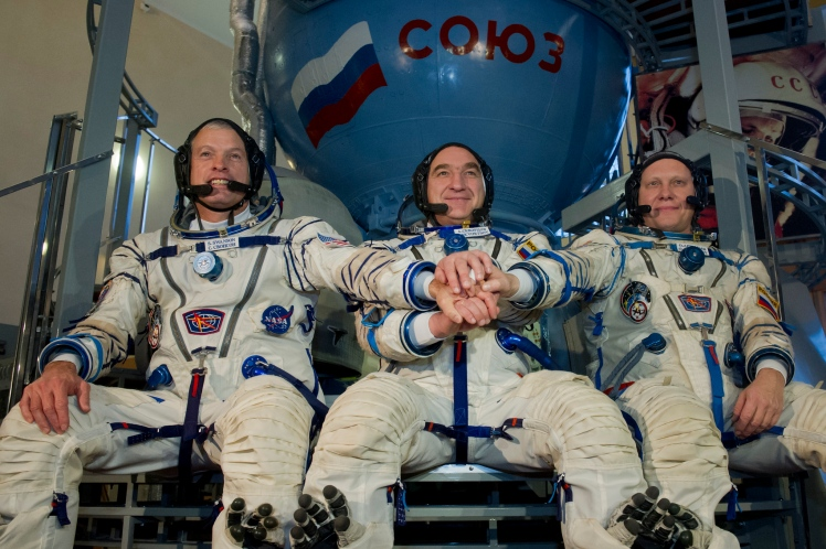 US NASA astronaut Steven Swanson (L) joins hands with Russian cosmonauts, Alexander Skvortsov (C) and Oleg Artemyev (R), in front of a mock-up of a Soyuz TMA spacecraft before their final preflight exam at the Gagarin Cosmonauts' Training Centre in Star City centre outside Moscow, on March 5, 2014. All three are scheduled to blast off to the International Space Station (ISS) from the Russian leased Kazakhstan's Baikonur cosmodrome on March 26, 2014. NASA chief Charles Bolden said today the US space agency's relationship with Russia remained normal despite the ongoing international crisis in Ukraine. AFP PHOTO (Photo credit should read -/AFP/Getty Images)