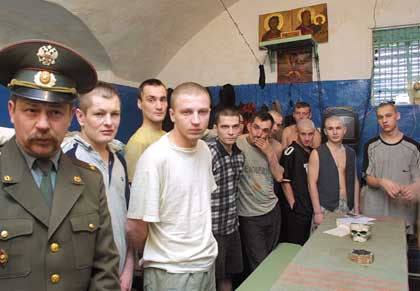 Prison warden Lt. Col. Leonid Siliverstov, left, stands in a cell with inmates, Thursday, June 6, 2002, at the Sergiev Posad pretrial holding facility about 80 kilometers (50 miles) north of Moscow. A Russian human rights group is trying to import a British system of volunteer monitors who would be prisoner advocates in Russia's overcrowded, disease ridden penal system. (AP Photo/Mikhail Metzel)